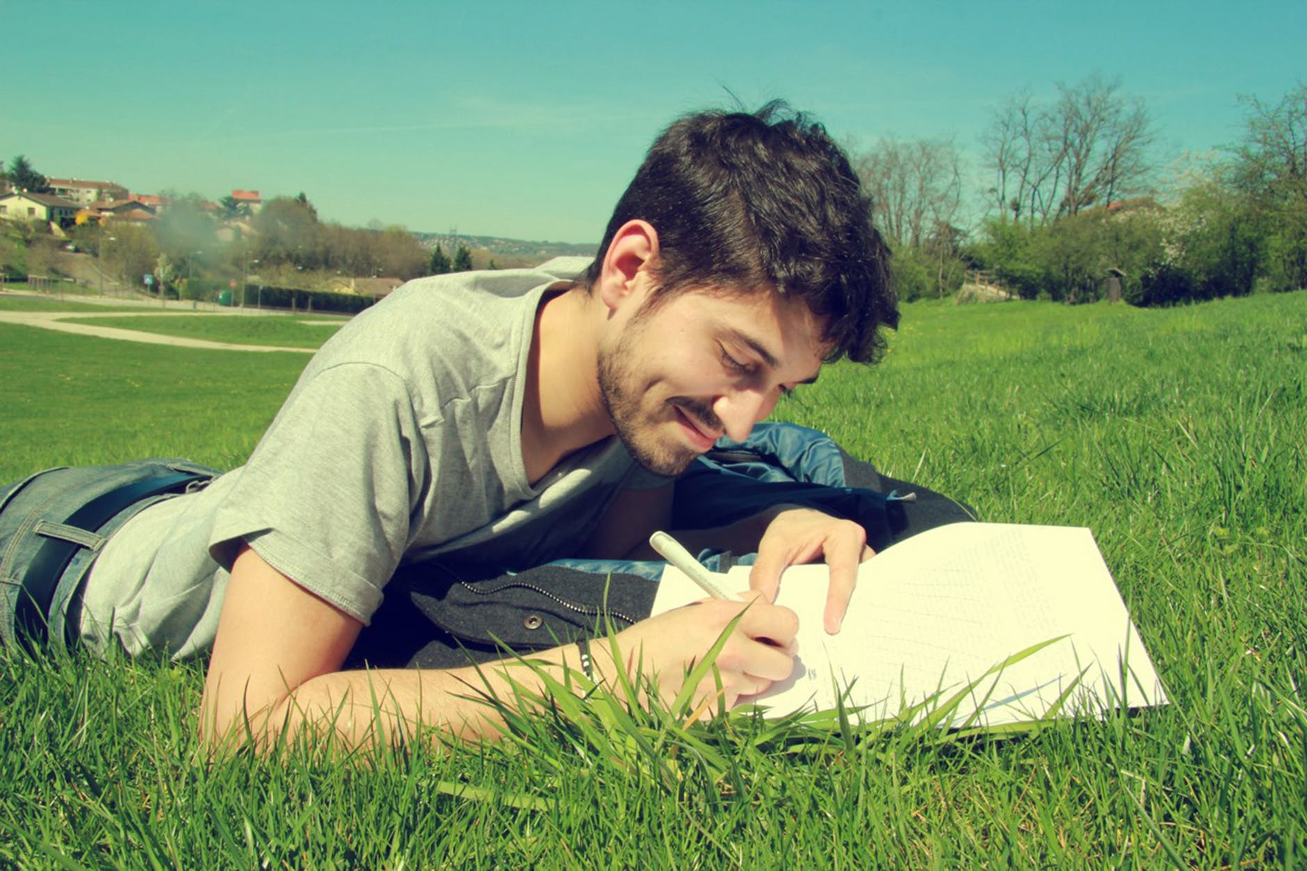 a man lies on the grass writing in the notebook