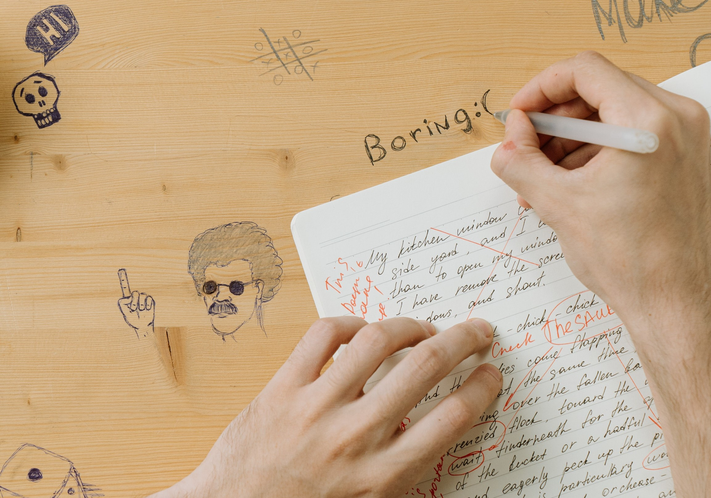 a boy is writing word boring on a desk